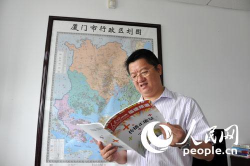 厦门市海沧区常委,宣传部长张谷在翻阅人民网福建频道的刊物(覃博雅