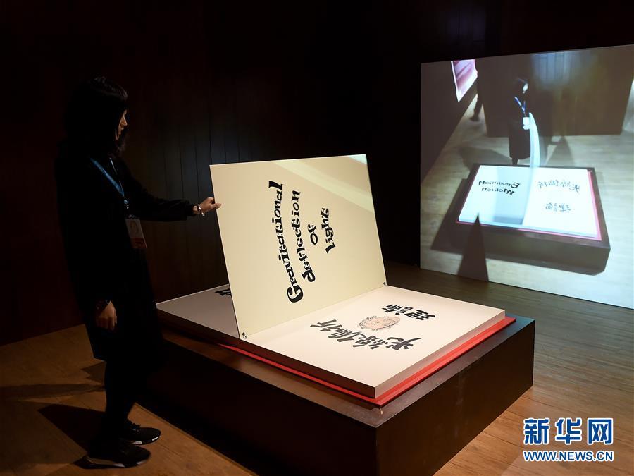 """1月11日,工作人员在展示""""爱因斯坦的书""""装置,让参观者体验爱因斯坦提出的物理现象。"""
