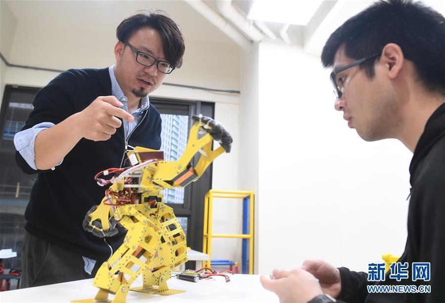 徐国峰(左)给公司员工讲授机器人的设计原理(3月27日摄)。